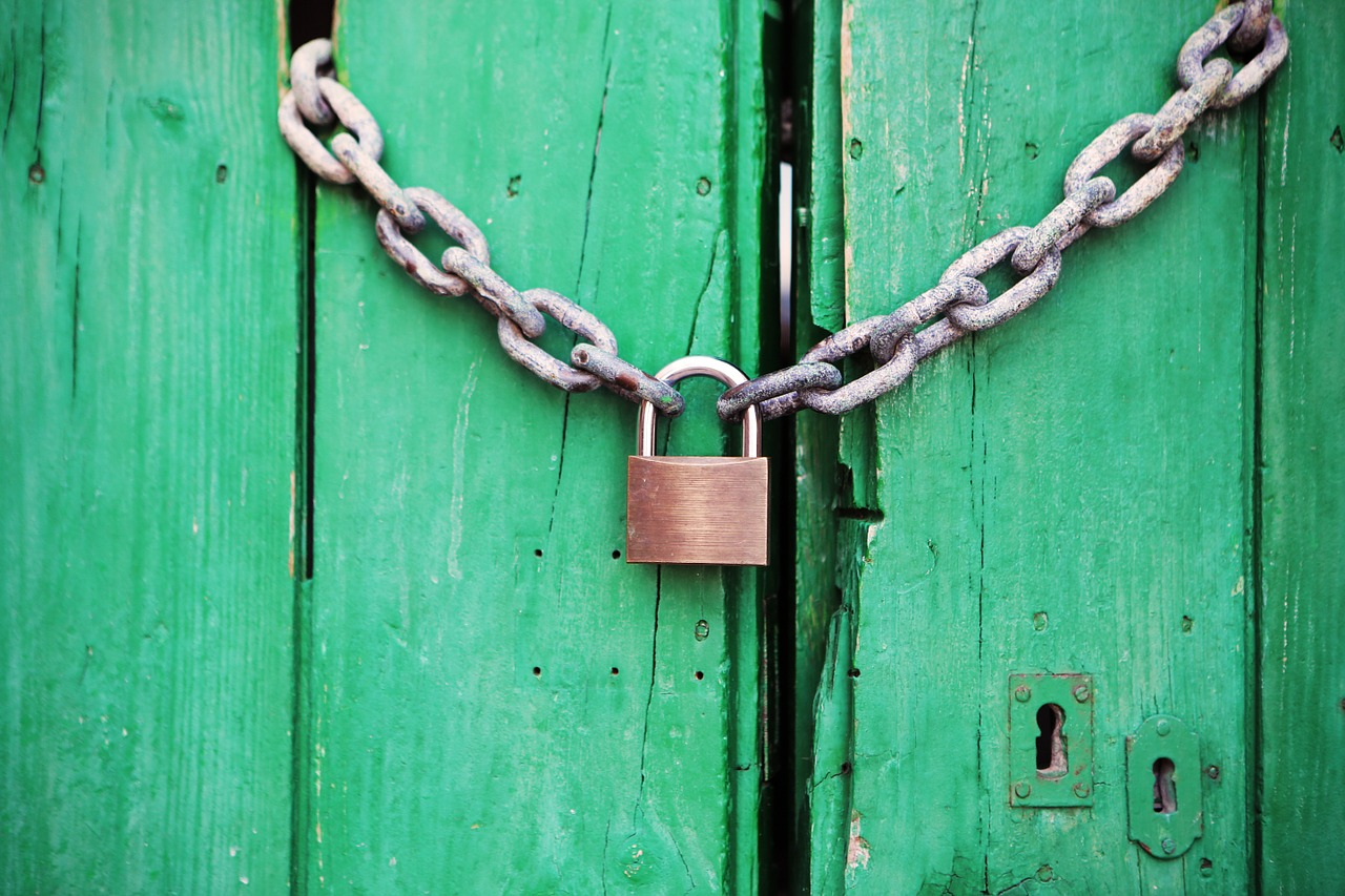 A green wooden door chained with a padlock attached